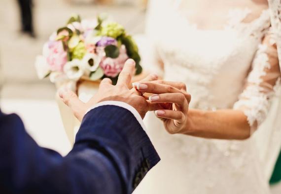 Невеста одевает кольцо жениху