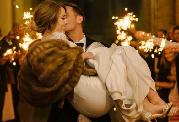 жених уносит невесту через коридор из огней